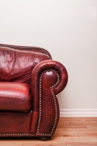 Luxurious Red Leather Couch Detail in front of a blank wall to ad your text, logo, images, etc.